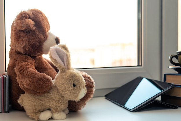 Cute teddy bear and bunny looking in tablet computer or touch pad at home on window.