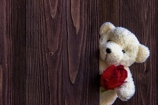 Cute teddy bear clutching a red rose in its arms on wooden background, copy space.  valentine concept