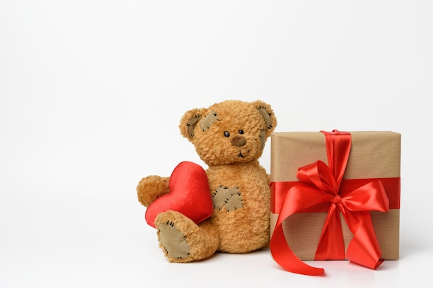 Cute teddy bear holding a red heart, next to a box with a gift tied with a red silk ribbon, white background