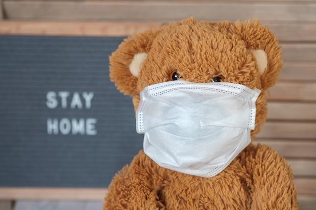 회색에 의료 마스크에 귀여운 테 디 베어 텍스트와 보드를 느꼈다 집에 머물. covid-19 코로나 바이러스 전염병 동안 가정 격리의 개념