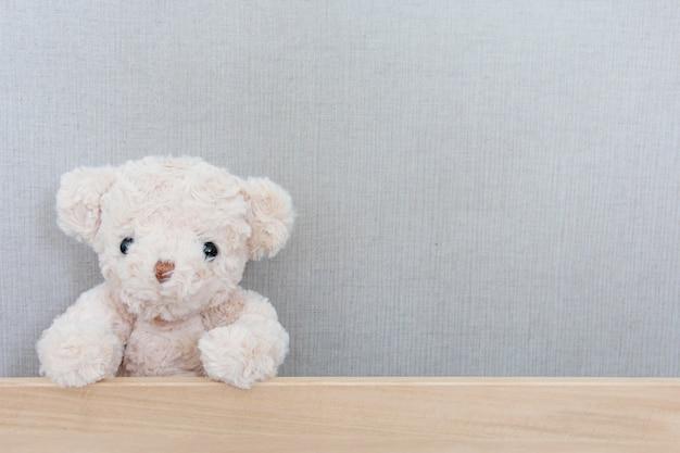 A cute teddy bear is catching on wood board on grey