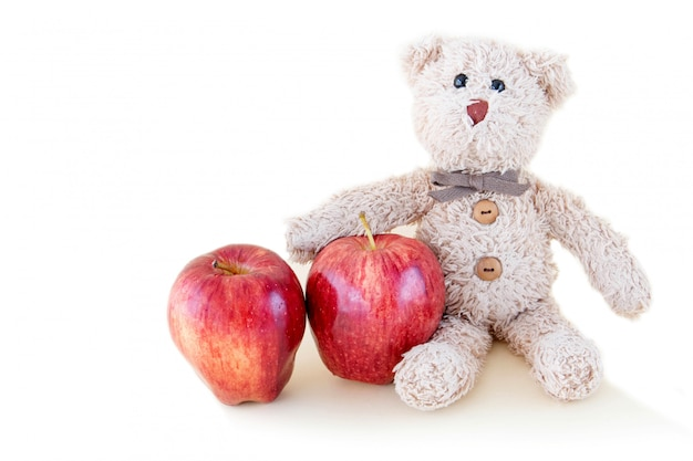 The cute teddy bear is eating a red apple fruit, it's yummy for diet healthy