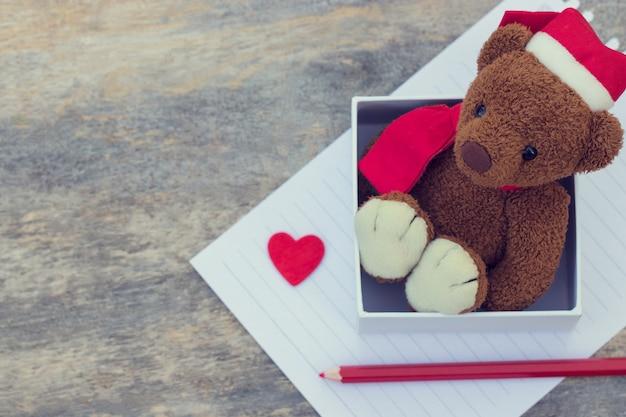 Милый плюшевый мишка в рождественской шапке внутри коробки с красным сердцем и карандашом на деревянном фоне