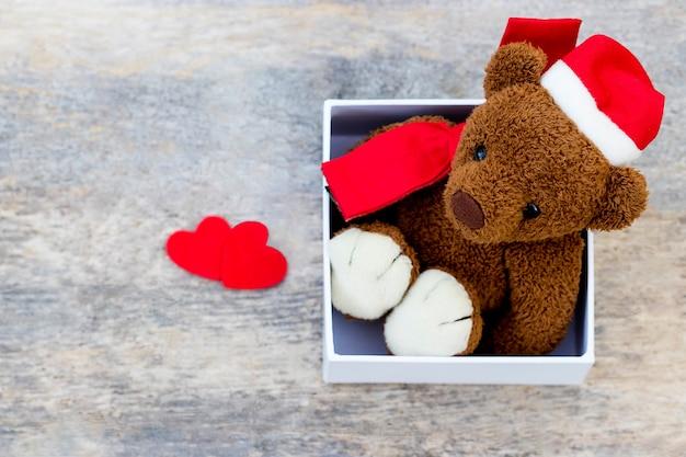 Милый плюшевый мишка в рождественской шапке внутри коробки с двумя сердечками на деревянном фоне