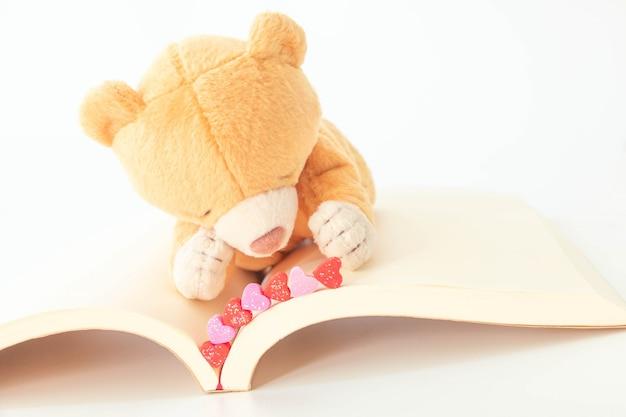 Милый плюшевый медвежонок с мини сердцем на книге, счастлив и усмехающся, концепция дня валентинки.