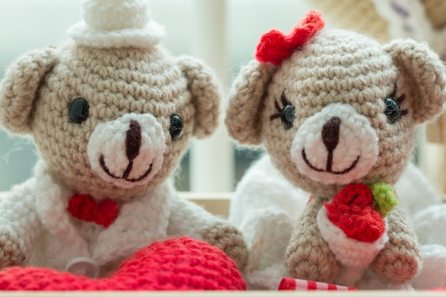 Cute teddy bears holding heart and red rose