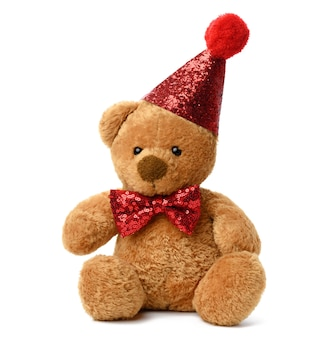 Cute teddy brown bear in a red festive shiny cap and a bow tie around his neck. toy isolated on white surface