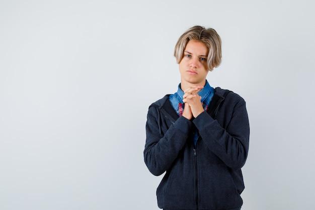 셔츠, 후드티를 입고 기도하는 몸짓으로 손을 꼭 잡은 귀여운 10대 소년과 희망찬 앞모습.