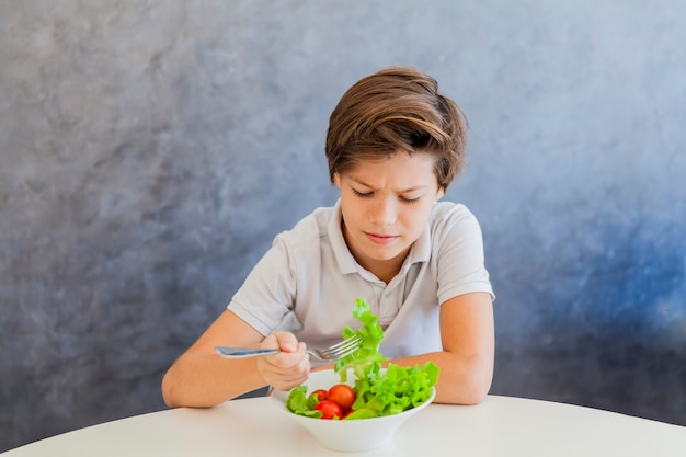 Cute teen boy eating salad
