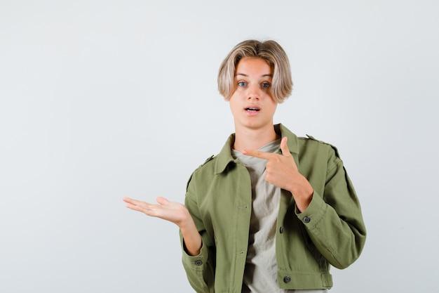 緑のジャケットを着たかわいい10代の少年が左を指して、手のひらを脇に広げて困惑しているように見える、正面図。