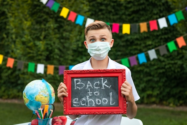 Симпатичный подросток мальчик в медицинской маске позирует с небольшой школьной доски
