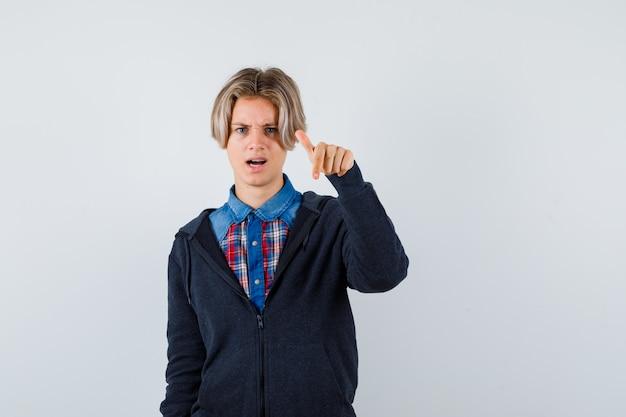 シャツを着たかわいい十代の少年、下を向いて困惑しているパーカー、正面図。