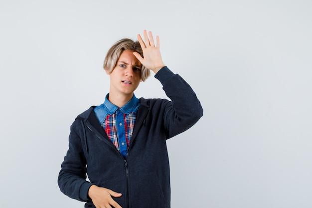 Милый мальчик-подросток в рубашке, толстовке с капюшоном, показывая ладонь и недоволен, вид спереди.