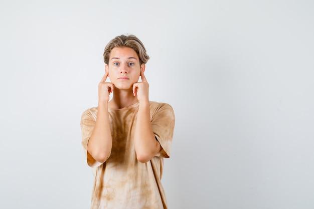 티셔츠를 입은 귀여운 10대 소년이 손가락으로 귀를 막고 초점을 맞추고 정면을 바라보고 있습니다.