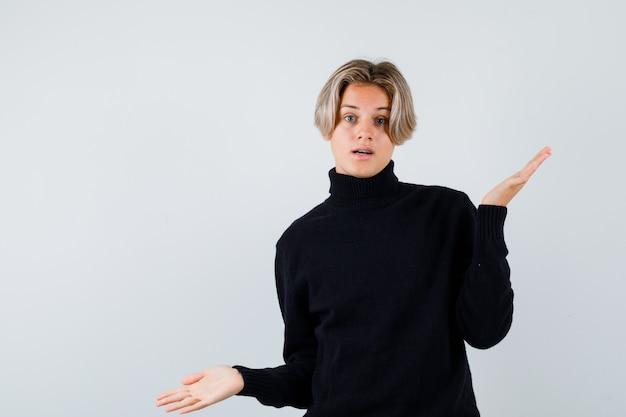 Симпатичный мальчик-подросток в свитере с высоким воротом показывает беспомощный жест и выглядит смущенным