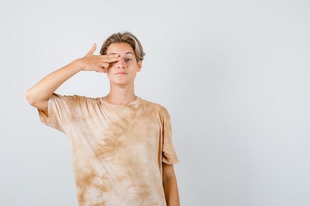 Ragazzo adolescente carino che tiene le dita sull'occhio in un gesto di pistola in maglietta e sembra sicuro, vista frontale.