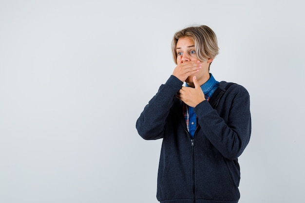 Cute teen boy keeping hand on mouth in shirt, hoodie and looking scared. front view.