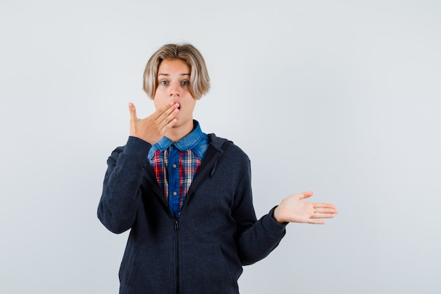 Cute teen boy keeping hand on mouth, spreading palm aside in shirt, hoodie and looking surprised , front view.