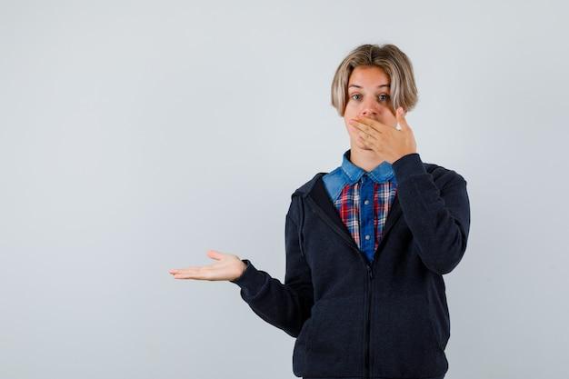 귀여운 10대 소년이 손을 입에 대고 셔츠, 후드티를 입고 손바닥을 옆으로 펼치고 놀란 표정을 하고 있습니다.