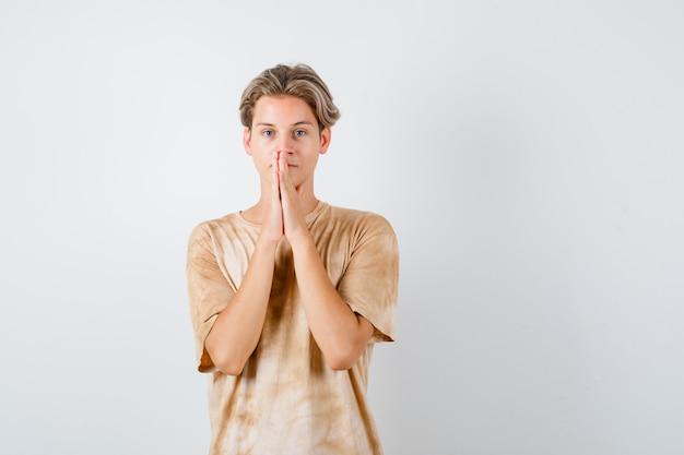 귀여운 십대 소년이 티셔츠를 입고 기도하는 손을 잡고 희망적으로 보입니다. 전면보기.