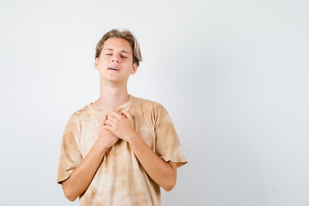 胸に手を置いて、tシャツで目を閉じて、夢のような正面図を見てかわいい10代の少年。