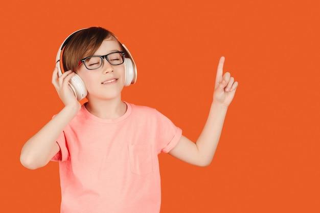 Милый мальчик-подросток, слушающий музыку в наушниках