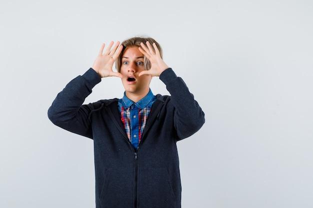 Симпатичный мальчик-подросток смотрит далеко с руками над головой в рубашке, толстовке с капюшоном и выглядит удивленным. передний план.