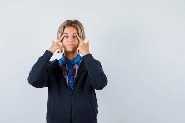 シャツ、パーカー、自信を持って、正面から眉を指してかわいい十代の少年。