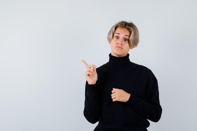 黒のタートルネックのセーターで左上隅を指して、陰気な、正面図を見てかわいい十代の少年。