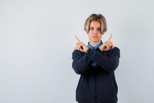 귀여운 십대 소년이 셔츠, 후드티를 입고 진지한 모습으로 정면을 바라보고 있습니다.