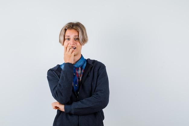 Ragazzo adolescente carino in camicia, felpa con cappuccio che tiene la mano sulla bocca e sembra perplesso, vista frontale.