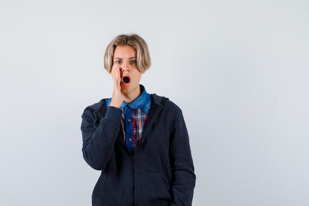 Ragazzo adolescente carino in camicia, felpa con cappuccio che tiene la mano vicino alla bocca e sembra agitato, vista frontale.