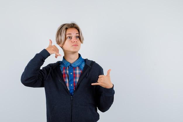 셔츠, 후드티에 전화 제스처를 보여주고 사려깊은 찾고 귀여운 십 대 소년. 전면보기.