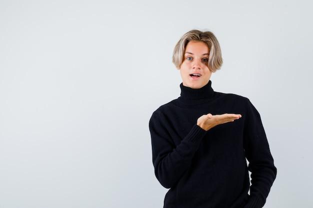 Ragazzo adolescente carino che mostra gesto di benvenuto in un maglione a collo alto e sembra allegro. vista frontale.