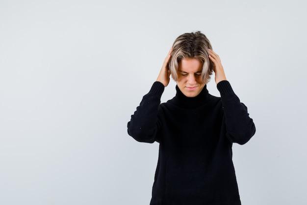 Симпатичный мальчик-подросток с руками на голове в черном свитере с высоким воротом и усталым взглядом. передний план.