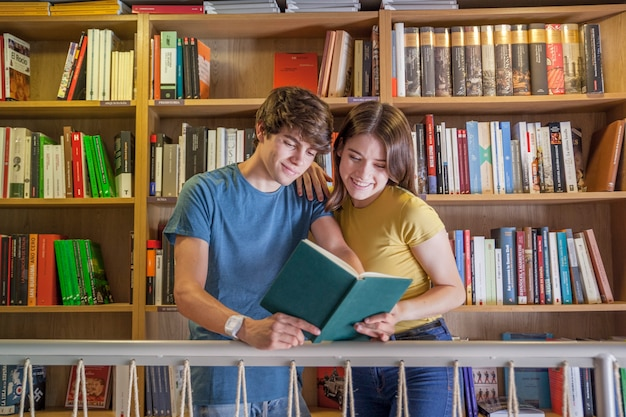 Cute teen couple reading in library