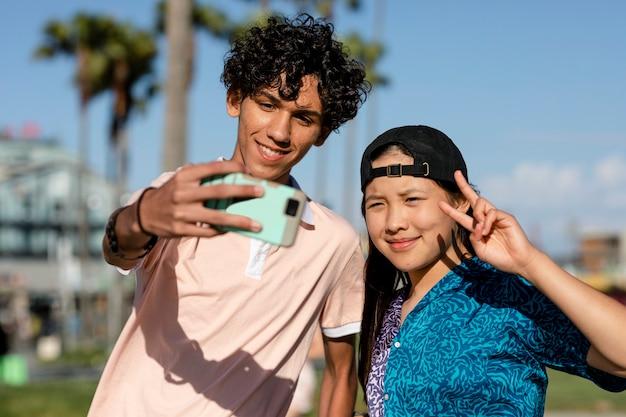 귀여운 십대 커플이 셀카를 찍고, 여름 로스앤젤레스 베니스 비치에서