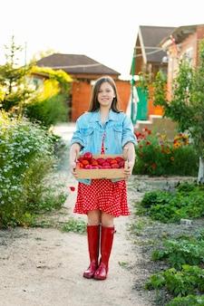 かわいい十代の少女と庭でトマトの木箱を保持