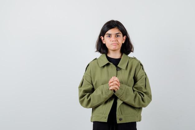 Ragazza teenager sveglia in giacca verde militare in piedi con le mani giunte e guardando dispiaciuto, vista frontale.