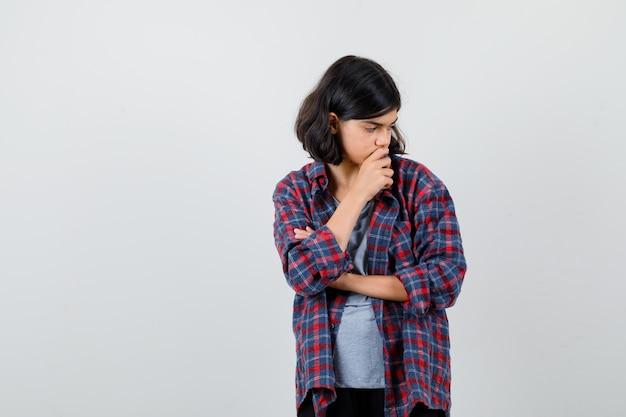 Ragazza teenager sveglia in camicia a quadri, guardando in basso e guardando pensieroso, vista frontale.