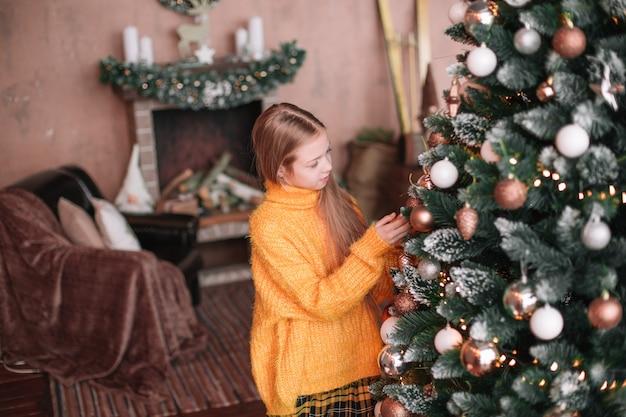 彼女のリビングルームでクリスマスツリーを飾るかわいい十代の少女