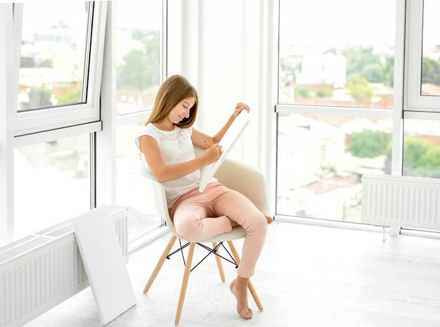 Симпатичная девочка-подросток, рисование карандашом в кресле