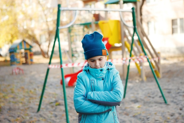 青いジャケットと緑の帽子をかぶったかわいい十代の少女は、胸に腕を組んで立って、悲しくて見下ろします