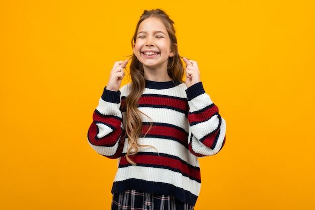 Симпатичная девочка-подросток в полосатом повседневном свитере спрашивает на желтом с копией пространства