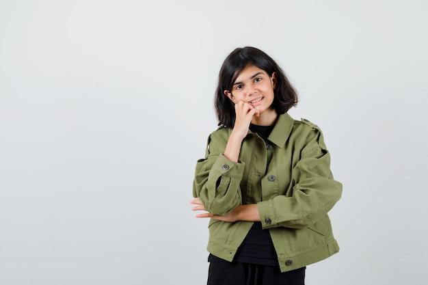 手に頬を傾けて陽気な、正面図を探している軍の緑のジャケットのかわいい十代の少女。