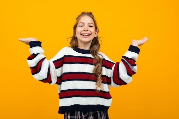 Милая девушка в полосатом свитере размахивает руками на оранжевом