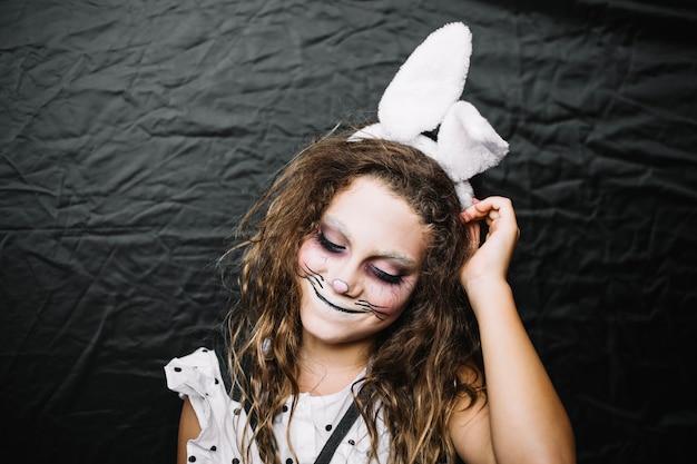 ウサギの顔のペンキでかわいい十代の少女