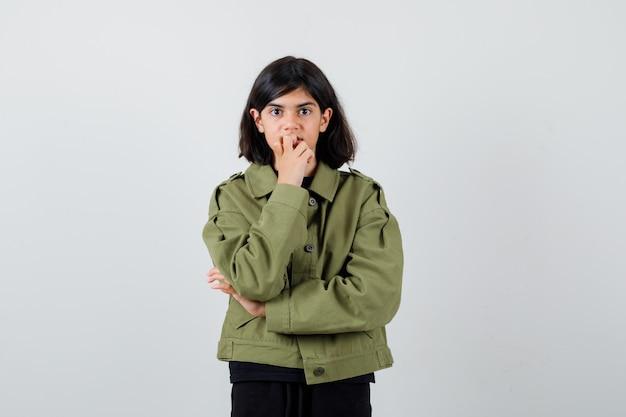 귀여운 10대 소녀가 녹색 군복을 입고 턱에 손을 대고 어리둥절한 표정을 짓고 있습니다.