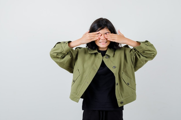 Cute teen girl keeping hands on eyes in army green jacket and looking excited , front view.
