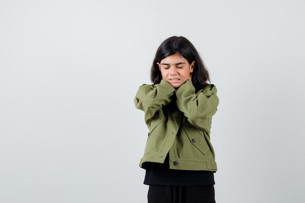 首に手を保ち、アーミーグリーンのジャケットで目を閉じて物思いにふけるかわいい十代の少女。正面図。